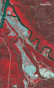 Taken by the WorldView-2, this image shows Fort McMurray before the fires. The infrared camera detects the living forest as bright red.