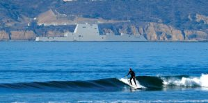 A San Diego surfer catches a wave in the foreground, as the Zumwalt sits pierside at its homeport.—MilitaryPress.com photo